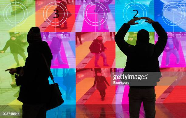 Visitors make shapes next to the 'Colour Me Beautiful' installation during the Winter Lights festival at the Canary Wharf financial shopping and...