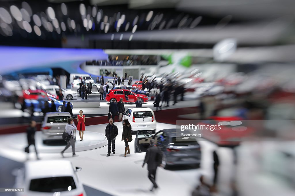 Visitors move between automobile stands inside an exhibition hall on the second day of the 83rd Geneva International Motor Show in Geneva, Switzerland, on Wednesday, March 6, 2013. This year's show opens to the public on Mar. 7, and is set to feature more than 100 product premiers from the world's automobile manufacturers. Photographer: Valentin Flauraud/Bloomberg via Getty Images