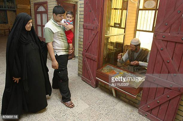 Visitors observe a market scene set up in the recently reopened AlBaghdadi Museum in the Iraqi capital Baghdad on September 1 2008 The museum...