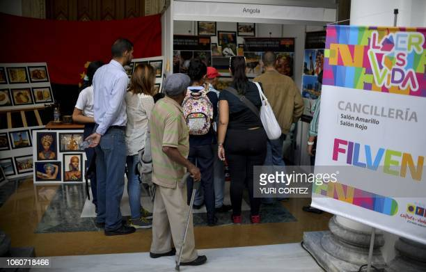 Visitors observe books during the International Book Fair of Venezuela in Caracas on November 12 2018 The main guest of FILVEN this year is Turkey