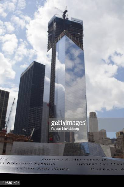 Visitors observe the inscribed names of those who perished in the 911 attacks at the 911 Memorial June 6 2012 in New York City In the background the...