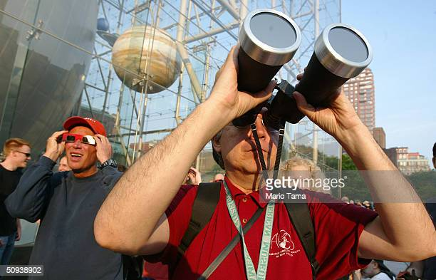 Visitors observe the planet Venus passing in front of the Sun with filtered optics at the American Museum of Natural History June 8 2004 in New York...