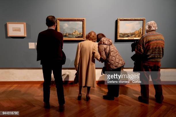 Visitors observes the paintings of the Venetian master Giovanni Antonio Canal, known as Canaletto, is displayed during the press preview of the...