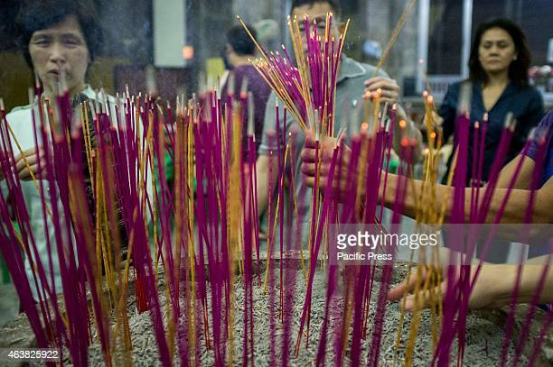 Visitors of the Buddhist Temple in Tondo light their incense as part of the rituals during the celebration of the Chinese New Year