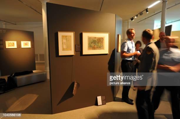 Visitors of the Bundeswehr Military History Museum look at exhibits of the special exhibition 'Krieg und Wahnsinn Kunst aus der zivilen Psychiatrie...