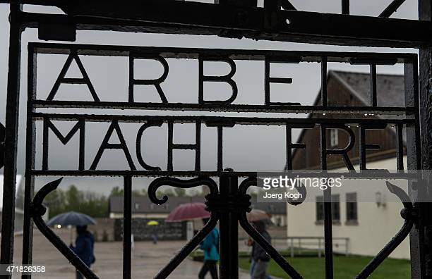 Visitors of the Dachau concentration camp pass by the historical concentration camp door sentence 'Arbeit macht frei' and attend the former camp site...