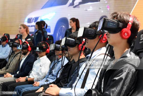 Visitors of the fair watch a presentation on virtual reality glasses on the second press day of the Paris Motor Show in Paris France 30 September...
