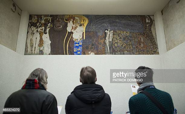 Visitors of the Secession Museum look at a part of the socalled Beethoven Frieze Painting entitled 'Kiss to the Whole World' by Austrian painter...