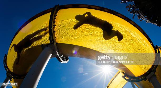Visitors of the 'Suedbad' public open air swimming pool slide down into the refreshing water on August 24 2016 in Hameln northern Germany / AFP / dpa...