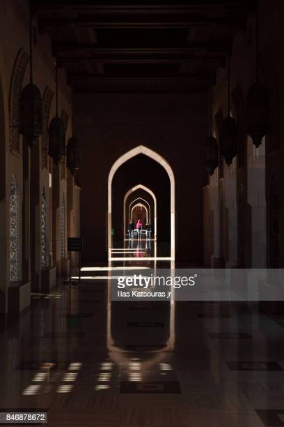Visitors of the Sultan Qaboos Grand Mosque in Muscat, Oman, walk along the Riwaq arches at the exterior courtyard