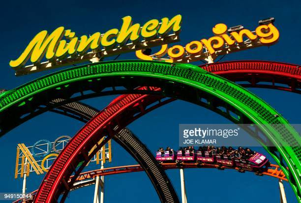 Visitors of Vienna's Prater amusement park take a ride on the Munchen Looping rollercoaster in Vienna Austria on April 20 2018