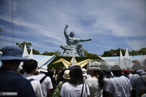 Visitors offer a prayer for the atomic bomb victims in front of the Nagasaki Peace Park in Nagasaki southern Japan on August 9 2018 Japan marks the...