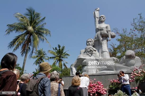 Visitors offer flowers at a war memorial dedicated to the victims of the My Lai massacre in the village of Son My during a ceremony marking the 50th...