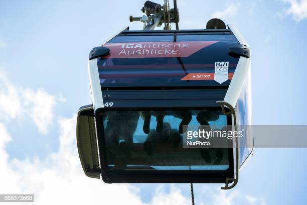 Visitors on a cable car with the glas bottom are pictured during the opening of the IGA 2017 in Berlin Germany on April 13 2017 The exhibition will...