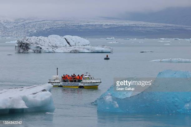 Visitors on a tour boat look at icebergs that have broken off of receding Breidamerkurjokull glacier, which looms behind, at Jokulsarlon lake on...