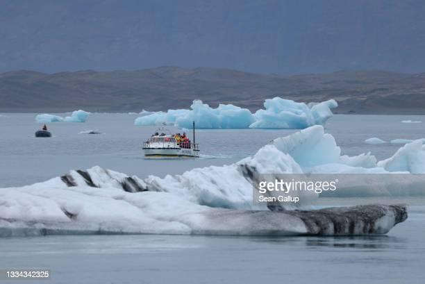 Visitors on a tour boat look at icebergs that have broken off of receding Breidamerkurjokull glacier on Jokulsarlon lake on August 15, 2021 near Hof,...