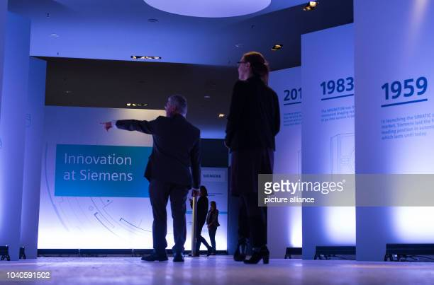 Visitors on their way to a Siemens press conference on the company's innovation strategy pass along a hallway featuring a timeline of the company's...