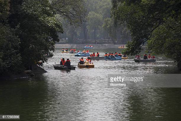 Visitors operate paddle boats and rowboats in an artificial lake inside the first section of Chapultepec Park in Mexico City Mexico on Saturday Sept...