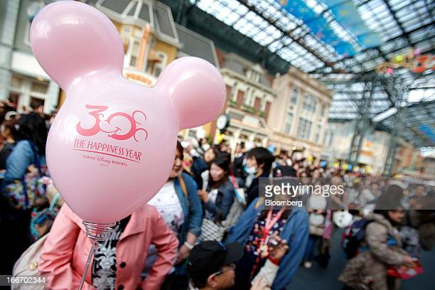Visitors pass a balloon as they walk through Tokyo Disneyland operated by Oriental Land Co in Urayasu City Chiba Prefecture Japan on Monday April 15...