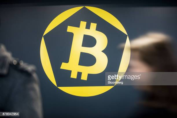 Visitors pass a bitcoin symbol on a glass panel at the offices of La Maison du Bitcoin bank in Paris France on Thursday Nov 23 2017 Zimbabwe where...