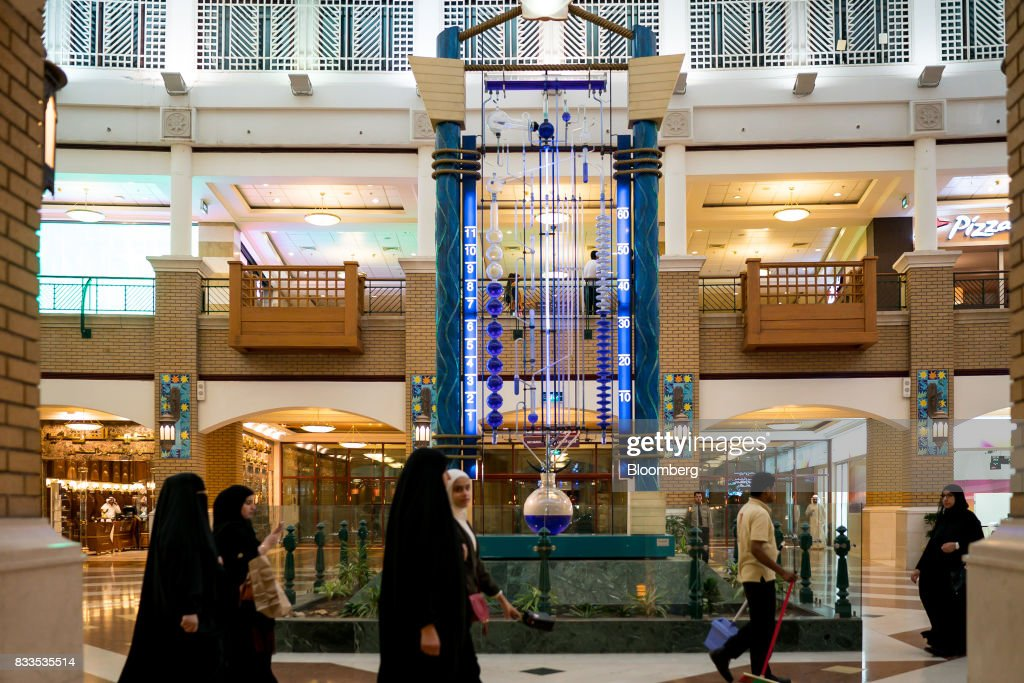 Visitors pass a cleaner while shopping in the Souq Sharq mall in Kuwait City, Kuwait, on Monday, Aug. 14, 2017. Kuwait will issue a tender to build the estimated $1.2 billion Dibdibah solar-power plant in the first quarter of 2018 as part of the countrys plans to produce 15 percent of power from renewable energy by 2030. Photographer: Tasneem Alsultan/Bloomberg via Getty Images
