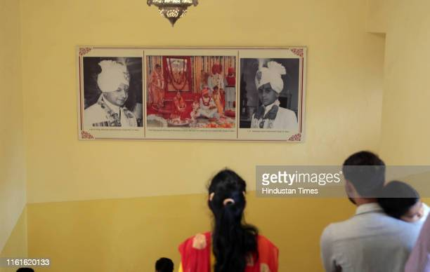 Visitors pass a collage depicting portraits of late erstwhile King of Jaipur Brigadier Bhawani singh and his adopted son former King Padmanabh, at...