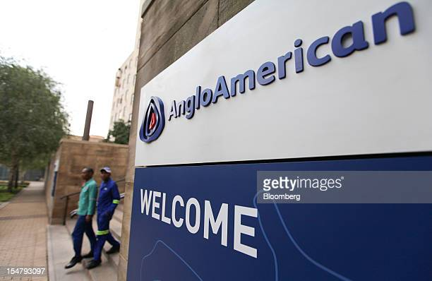 Visitors pass a sign at the entrance to the offices of Anglo American Plc in the Marshalltown district of Johannesburg South Africa on Friday Oct 26...