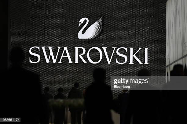 Visitors pass a Swarovski luxury goods booth on the opening day of the 2018 Baselworld luxury watch and jewelry fair in Basel Switzerland on...
