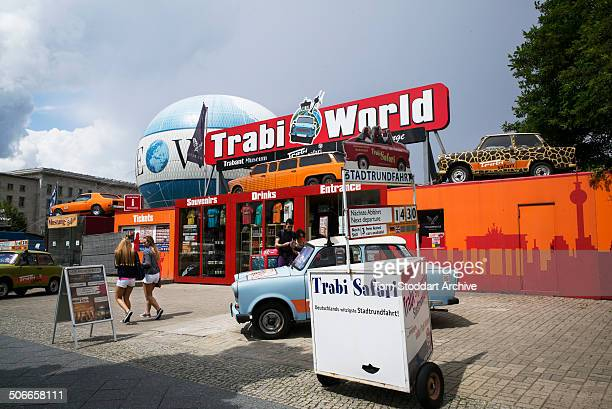 Visitors pass a tourist attraction offering a Trabant 'experience' near Checkpoint Charlie At Midnight on November 9th East Germany's Communist...