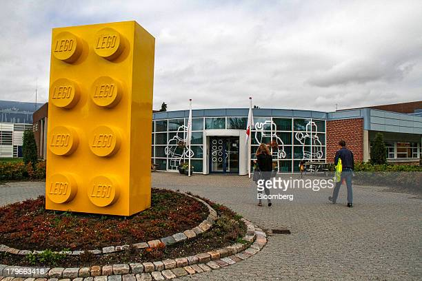 Visitors pass a toy brick artwork outside the entrance to the headquarters of Lego A/S in Billund Denmark on Thursday Sept 5 2013 Lego the Danish...