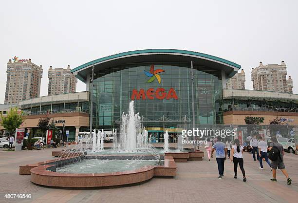 Visitors pass a water fountain as they approach the Mega shopping center in Almaty Kazakhstan on Thursday June 25 2015 Kazakhstan's central bank...