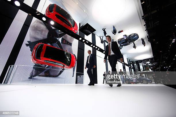Visitors pass an Opel Corsa automobile produced by Adam Opel AG suspended on a wall during the preview day at the Paris Motor Show in Paris France on...