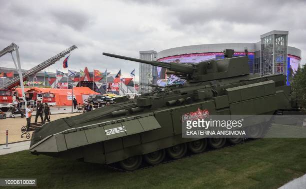 Visitors pass by a Russian Armata tank T15 in Kubinka Patriot Park outside Moscow during the International MilitaryTechnical Forum Army2017 on August...