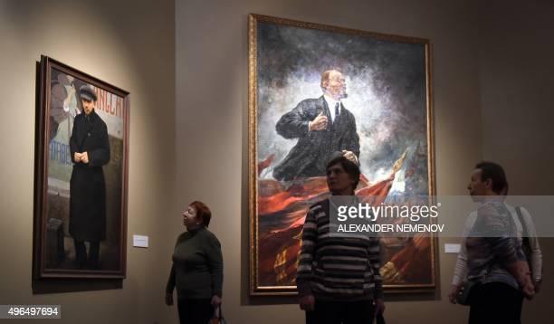 Visitors pass by Soviet artist Aleksandr Gerasimovs painting Lenin on the Tribune displayed in the exhibition Romantic Realism Soviet Art of 19251945...