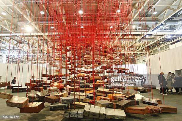Visitors pass by the artwork of the artist AChiharu Shiota Accumulation searching for Destination during the press preview for Art Basel at Basel...