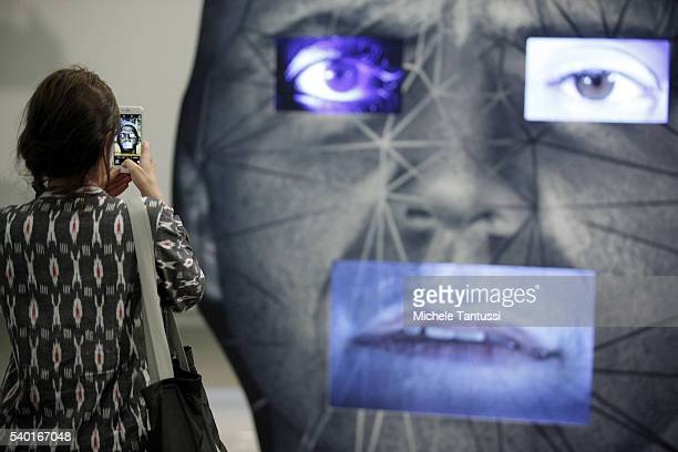 Visitors pass by the artwork of the artist Tony Oursler Template during the press preview for Art Basel at Basel Messe on June 14 2016 in Basel...