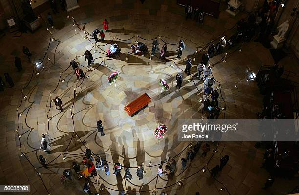 Visitors pass by the casket of Rosa Parks as she lies in honor at the Capitol Rotunda October 30 2005 in Washington DC Parks is the first woman and...