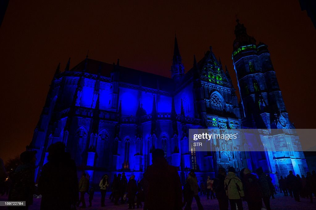 Visitors pass by the illuminated St.Elizabeth's Cathedral during the opening ceremony of the European capital of culture Kosice 2013, in Kosice on January 19, 2013.