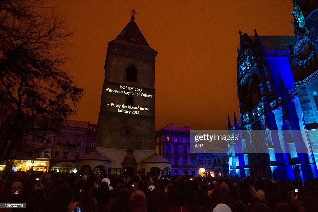 Visitors pass by the illuminated Urban's tower during the opening ceremony of the European capital of culture Kosice 2013, in Kosice on January 19, 2013.