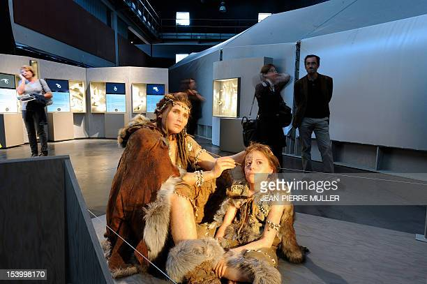Visitors pass by wax figures representing the CroMagnon humans the early Homo sapiens sapiens such as those who painted in the Lascaux caves...