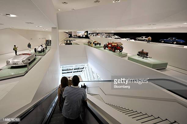 Visitors pass displays of vintage automobiles at the Porsche museum in Stuttgart Germany on Friday June 22 2012 Porsche AG which is jointly owned by...