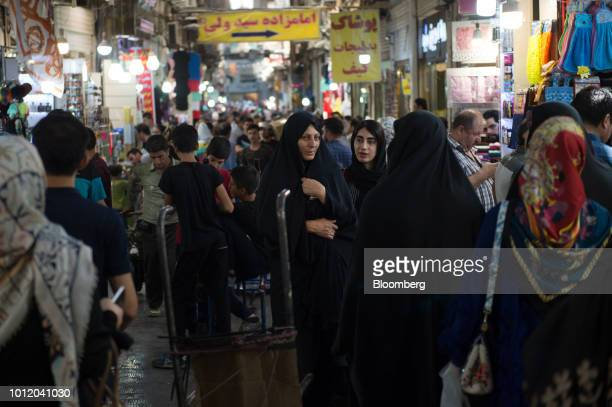 Visitors pass stores in a crowded retail arcade inside the Grand Bazaar in Tehran Iran on Monday Aug 6 2018 Irans central bank acting on the eve of...