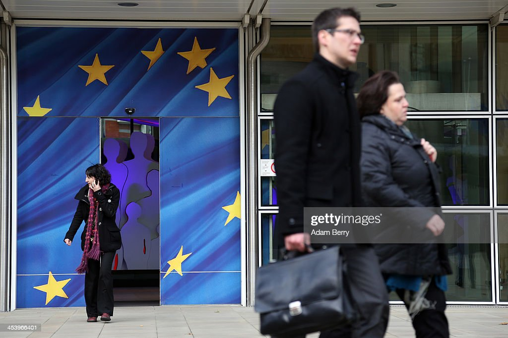 Visitors pass the Berlaymont building of the European Commission (EC) on December 6, 2013 in Brussels, Belgium. The European Commission is responsible for the implementation and maintenance of the execution of the European Union's policies.