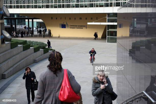 Visitors pass the Berlaymont building of the European Commission on December 6 2013 in Brussels Belgium The European Commission is responsible for...