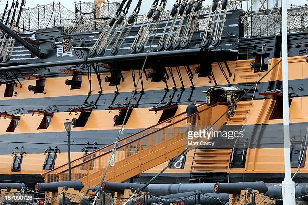 Visitors pass the historic ship HMS Victory displayed in the Historic Dockyard besides the BAE systems yard at the HM Naval Base in Portsmouth...