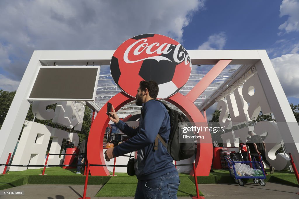 Visitors pass the promotional pavilion for Coca-Cola Co. ahead of the FIFA World Cup outside the Luzhniki stadium in Moscow, Russia, on Wednesday, June 13, 2018. According to an April report from the organizing committee, the total amount spent on preparations is 683 billion rubles, or about $11 billion at the current exchange rate. Photographer: Andrey Rudakov/Bloomberg via Getty Images