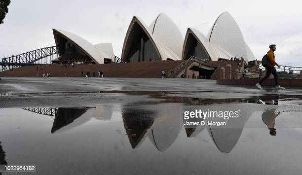 Visitors pass the sails of the iconic Opera House as they are reflected in a puddle of water after a rain shower on August 25 2018 in Sydney...
