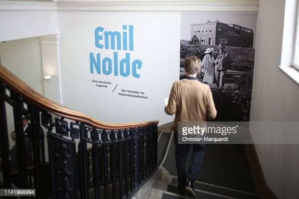"""Visitors passing by the billboard of the exhibition during the preview of the exhibition """"Emil Nolde - Eine deutsche Legende. Der Kuenstler im..."""