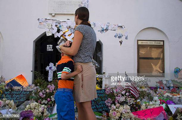 Visitors pause outside Emanuel AME Church in Charleston South Carolina on June 23 2015 Police captured the white suspect in a gun massacre at one of...