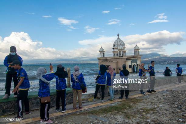 Visitors pay attention to the Floating Mosque which collapsed into the sea due to the tsunami struck at Kampung Lere Beach Palu Central Sulawesi...